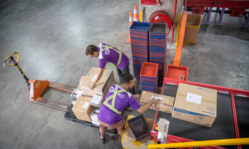 Employees handle packages at Qoo10 warehouse in Singapore.